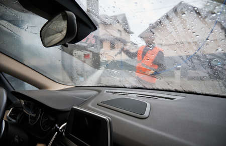 Close up view from inside car through wet windshield. On blurred background car wash specialist in bright uniform with high pressure water gun in his hands, apartment buildings.