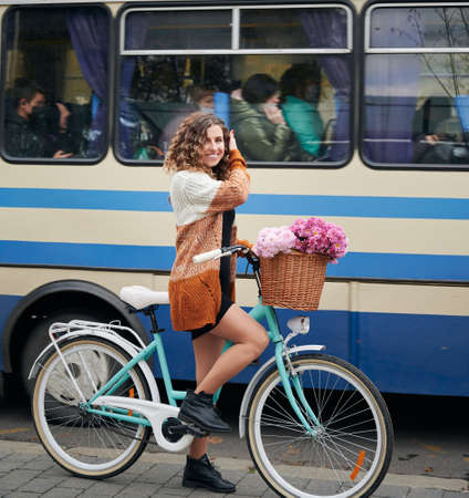 Close up of smiling young woman with curly hair riding bicycle with bouquet pink fresh flowers on blue and white bus background. Concept of walking with bicycle in cetre city.