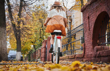 Back view of woman travelling by vintage cycle down street. Female wearing brown hat and cardigan is riding bike near autumn park. Concept of cyclist.