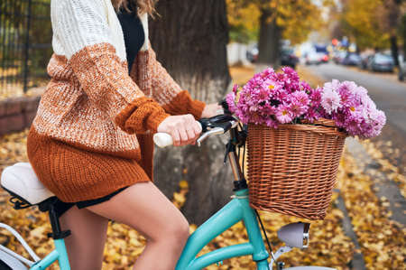 Close up of female bicyclist in knitted cardigan riding bike with flowers on autumn street. Young woman on bike with beautiful bouquet in front basket.