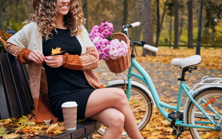 Elegant young woman holding autumn leaf and smiling while sitting on bench with cup of coffee near bicycle. Cheerful female person resting outdoors near bike with flowers in basket.