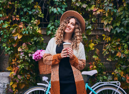 Curly woman posing with vintage bicycle and cup of coffee near green plant wall. Female wearing brown hat and cardigan is travelling by bike with big basket of pink camomiles. Concept of leisure.
