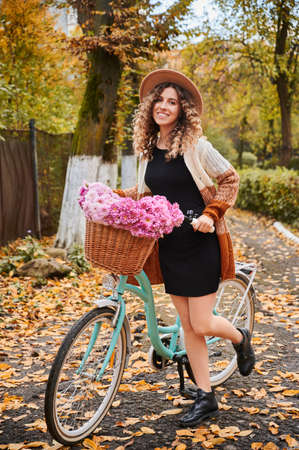 Front view of happy smiling woman with curly hair in beige hat standing with cute blue bicycle and wicker brown basket with pink beautiful flowers. Concept of walking with stylish bicycle in park.