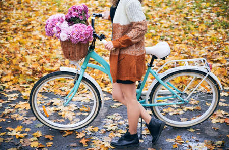Side view of city retro womens bicycle with wicker brown basket filled pink flowers. Cropped girl keeping bike on asphalt trail on the background of glade, almost fully covered with fallen leaves. 版權商用圖片