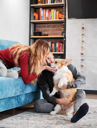 Young pair caressing their pet at home in modern living room. Husband sitting on rug and hugging dear dog, wife sitting on blue sofa and leaning to him petting under chin.