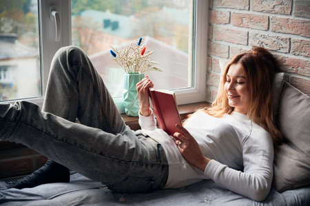 Side view of beautiful woman lying on windowsill bed and reading book. Pretty female is resting near window and reading. Concept of leisure.