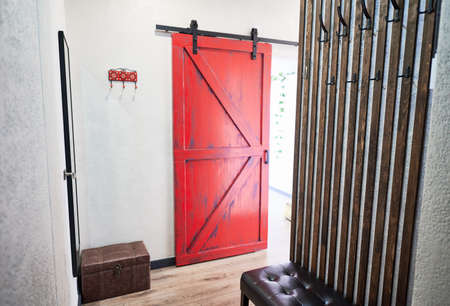 View of red door in corridor with big mirror on wall and ottoman. Interior of hallway of appartment in loft style with wooden flooring. Concept of loft style.