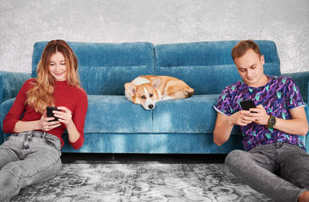 Smiling young woman and man sitting on the floor and using mobile phones while adorable Corgi resting on sofa at home. Family dog is bored, waiting for person to pay attention or play with him.