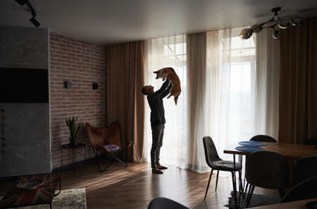Full length of young man holding cute Corgi dog while standing by the window of cozy apartment. Handsome man raising adorable dog in the air while spending time at home.
