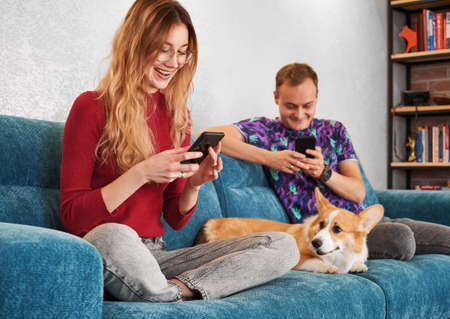 Cheerful young woman and man using mobile phones and smiling while sitting on sofa with adorable Corgi. Beautiful couple surfing the internet on smartphones while spending time with cute dog at home. 版權商用圖片