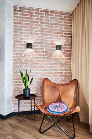 View of restplace in loft appartment with big wooden chair. Interrior of modern flat with brick wall with two lampshades. Concept of comfortable design.