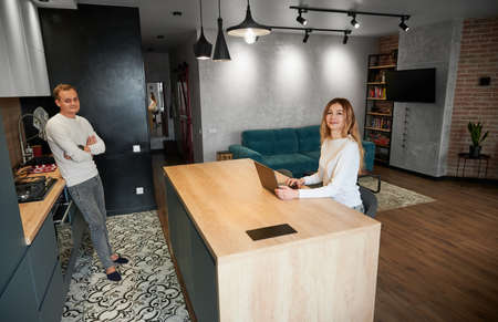 Young woman and man working or studying on laptop with good mood in modern kitchen at home. Concept of working at home in modern kitchen with beautiful interior.