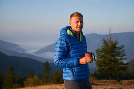 Portrait of man hiker standing on the background of panoramic foggy mountains, holding tourist cup and basking in the sun on cool sunny morning.