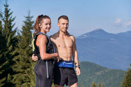 Portrait of trail runners - nice guy with naked torso hugging his pretty girl with small tourist backpack standing on background of green trees, mountains and light blue sky.