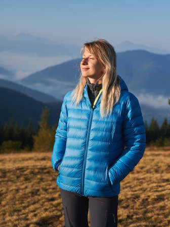 Young woman with satisfied expression and closed eyes standing on grassy meadow on the background of misty mountain hills at bright autumn morning.