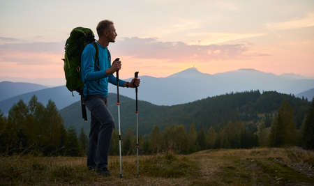Man traveler against backdrop of mountain hills and pink cloudy evening sky at sunset. Hiker with trekking poles and touristic backpack standing on glade and admiring mountain fairytale landscape.