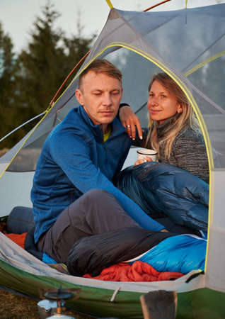 Family couple of mountain campers resting on glade in tent. Husband, lowering his eyes, thinking about next hike. Wife, holding cup, leaning on mans shoulder and smiles enjoying scenery. 版權商用圖片