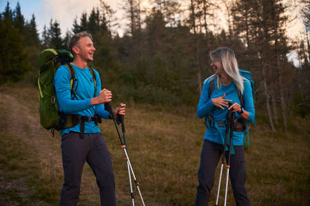 Couple of hikers laughing together while walking outdoors on forest background. Married pair of tourists smiling at each other. Concept of travelling, hiking, active leisure. 版權商用圖片