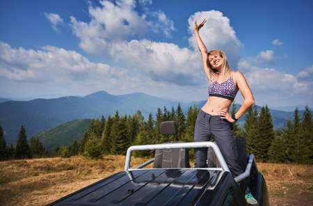 Young woman in bright sports bra with happy face expression standing on body of SUV and holding one hand on waist and other raising up. Beautiful mountain landscapes on the background. 版權商用圖片