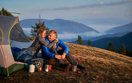 Young couple in love hikers exploring new places together. Attractive woman and man spending time on nature in mountain campsite sitting near touristic tent on grassy hill.