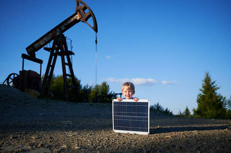 Portrait of cheerful boy with solar battery smiling at camera during education time at petroleum station with pump derrick on background, happy child with panel for product alternative green energy