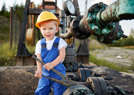 Adorable little boy looking at camera and smiling while tightening bolt on pipe in oil field. Cute kid in construction helmet using industrial wrench while repairing pump jack pipe outdoors.