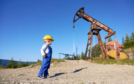 Young child standing in workwear and protective yellow helmet on stone surface. Boy watching at working oil pumpjack on the background of blue clean sky.