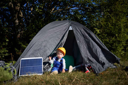 Portrait of young boy in construction helmet resting in tourist tent. One solar battery located near tent in which sitting child with concentrate face expression outdoors. 版權商用圖片