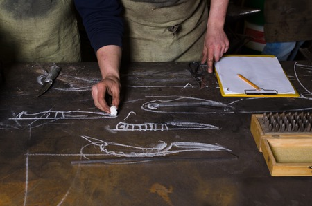 forge: Table in a forge. Planning design of knife. Craftsman stands near the table Stock Photo