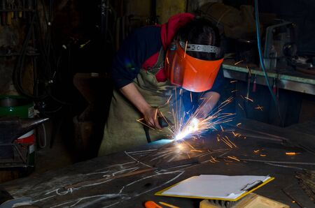welds: a man in a mask welds metal parts inside. On the table a notebook