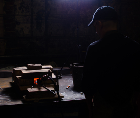 billet: a man watches the heated billet in the furnace of a knife. The horn is made