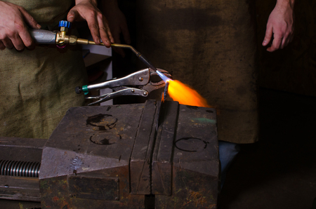 metall: Man keep welding tool in hands and heating metall
