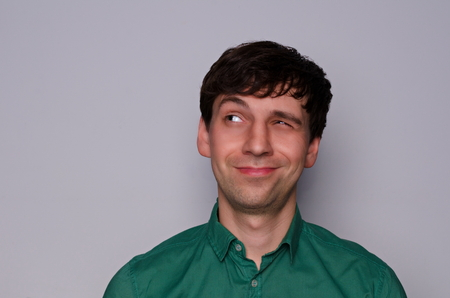 scheming: leer European man in a green shirt on a neutral gray background. Dodgy emotion. Look up to the left with one eye half-closed
