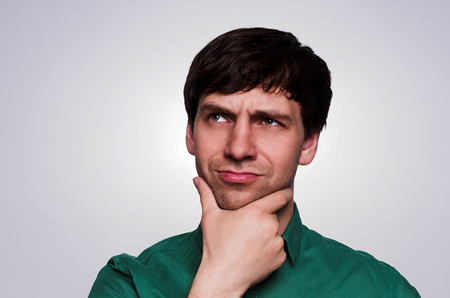 business skeptical: Portrait European thinking man in a green shirt on a neutral gray background. Emotion reflects the thinking process. Man look up to the left, eyes narrowed, chin hand props