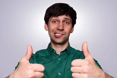 teeths: Young man in green shirt have crazy smile and show like by two hands. Idiot smile with white teeths. Man on neutral grey background. Crazy smile emotion. Stock Photo