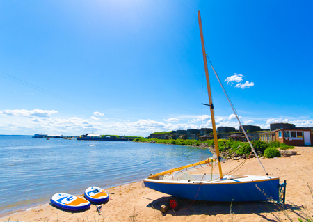 Sunny coast background with blue sky. boat and two paddle boards on the sand. Stock Photo