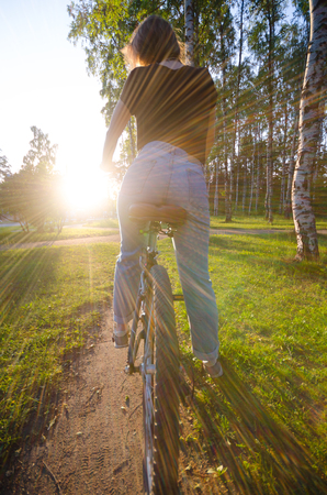 bycicle: Back view to the girl by bycicle. Health outdoor concept. Walk by bike in park, when sun goes down. Stock Photo
