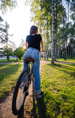 bycicle: Woman ride by bycicle in park in the evening. View on girls back. Stock Photo