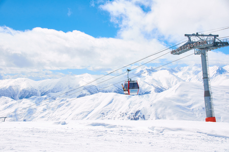 concept of ski resort in mountans of new ride season. Cabine lift for snowboard riders with blue bright sky background. Free place for advertising text or logo. Extreme sport fun rest.
