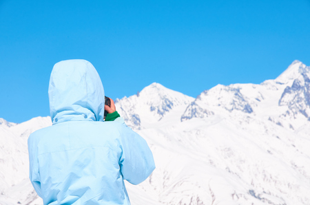 clambering: Girl take picture of winter landscape with mountains peaks, white snow, blue sky on highest point of ski resort in sunny day.