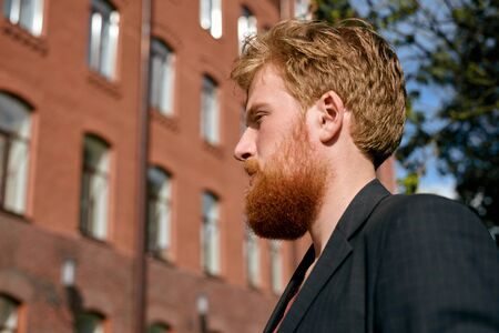 Close up portrait of redhead man near red brick business building. Thinking hipster in suit. Concept of adult life. Ready so a deal. Stock Photo