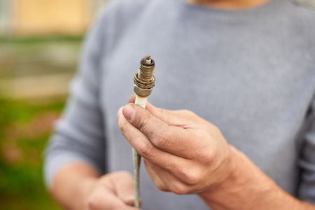 Close up plug spark in hands of mechanic