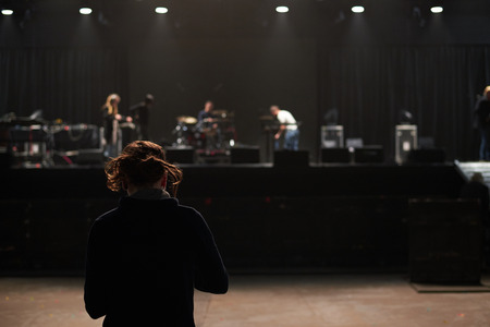 Man adjusts the sound before the concert. Back view on the scene. Stock Photo