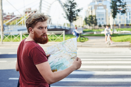 Tourist explore new city. Hansome man with big beard in red t shirt walk in the city to learn more about it. Guy stay in font of crosswalk and look back