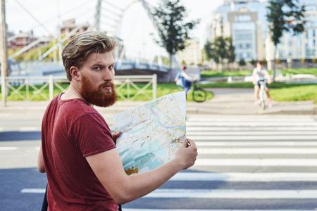 Turista explorar nueva ciudad. Hansome hombre con gran barba en camiseta roja caminar en la ciudad para aprender más sobre él. El tipo se queda en la fuente del paso de peatones y mira hacia atrás