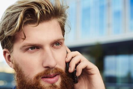Close up hight detailed handsome man face talk by mobile phone and look forward. Business conversation in process. Stock Photo
