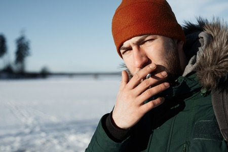 Smoking man outdoor with winter field and forest background. Guy look to the camera with a cigarette. Free space for advertising text or goods.