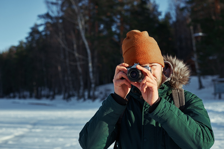 contryside: Close up portrait of photographer with vintage camera. Bearded backpacker making photo in sunny day contryside with snowy field and green forest. Travel concept with free space for advertising.