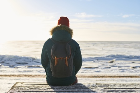 Backpacker sit and look to the sea. Dreaming concept. Frozen winter sea. Open space to the horizont. Freedom feeling. Place for thinking. Stock Photo