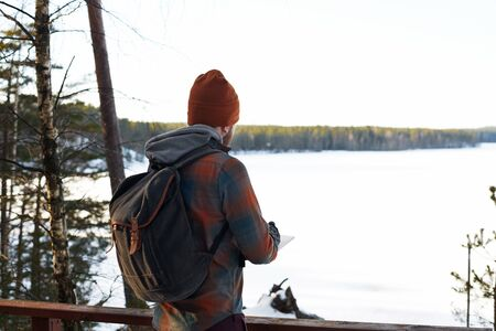 anorak: Backpacker near forest lake in winter period.